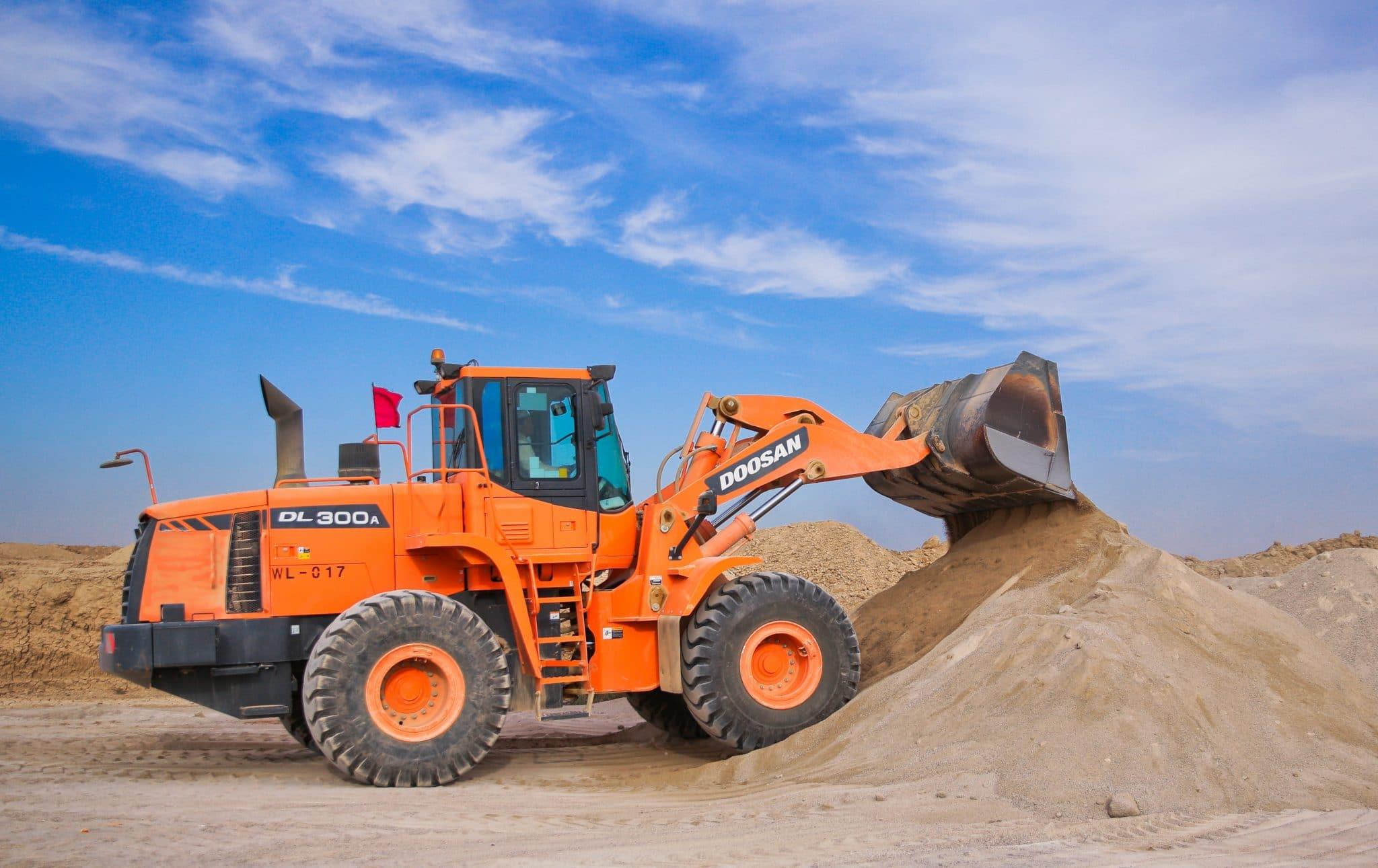 orange excavator on brown hill